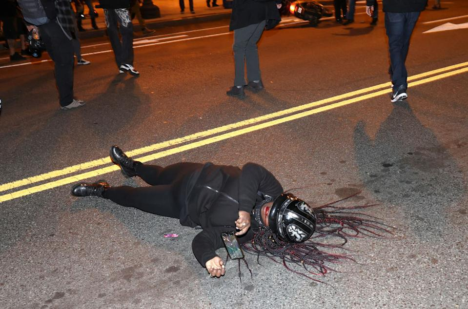 A Black Lives Matter protester bleeds from the mouth as she lays in the middle of the street. Source: Getty