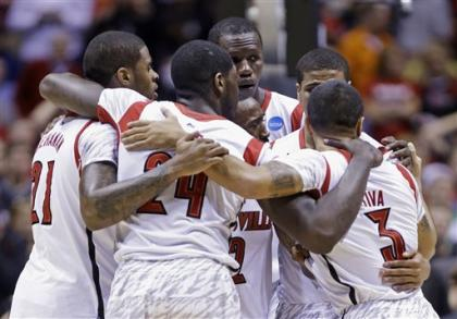 Louisville players huddle as guard Kevin Ware is treated for his injury. (AP)