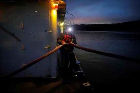 Twenty-one year-old deckhand trainee Jacob Bumgarner holds a line while wearing a headlamp shortly before sunrise on Campbell Transportation Company's towboat MK McNally on the Ohio River near, Cincinnati, Ohio, U.S., September 14, 2017. REUTERS/Brian Snyder