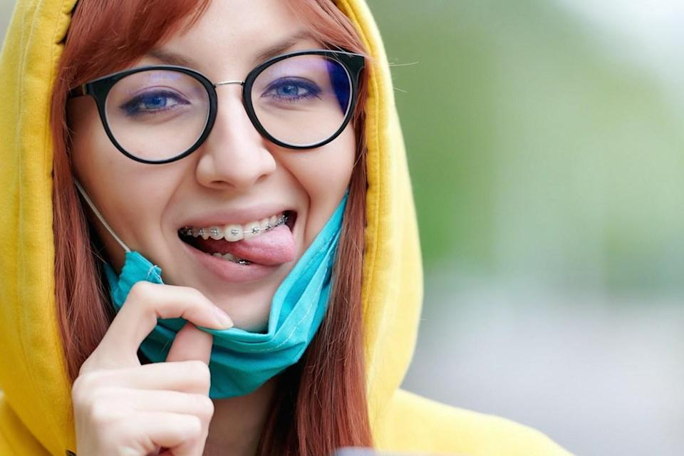 with glasses and braces joyfully removes the medical mask from her face, mimics and shows her tongue