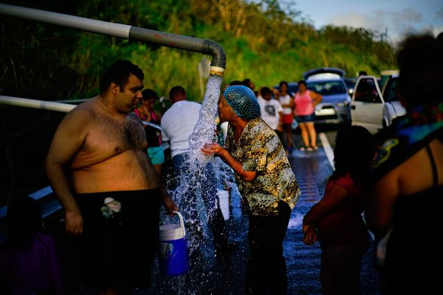 <p>People who lost access to water in the wake of Hurricane Maria gather at pipes carrying water from a mountain creek, on the side of the road in Utuado, Puerto Rico, Saturday, Oct. 14, 2017. (Photo: Ramon Espinosa/AP) </p>