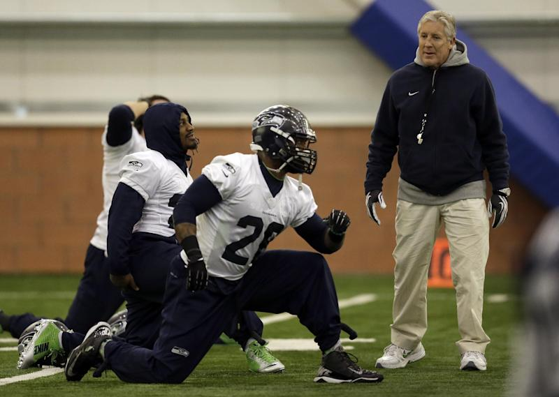 Seattle Seahawks head coach Pete Carroll, right, talks with running back Marshawn Lynch, left, and fullback Michael Robinson while they warm up at the start of NFL football practice Thursday, Jan. 30, 2014, in East Rutherford, N.J. The Seahawks and the Denver Broncos are scheduled to play in the Super Bowl XLVIII football game Sunday, Feb. 2, 2014. (AP Photo)