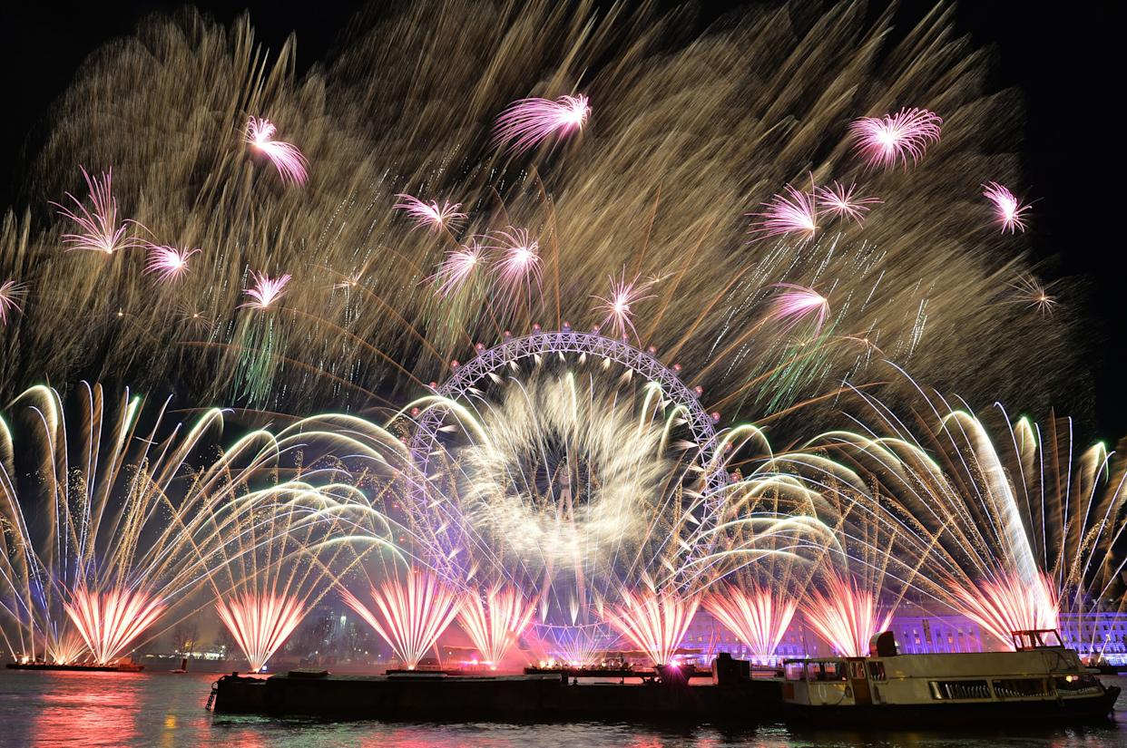 Fireworks light up the sky over the London Eye in central London during New Year's celebrations. (Photo: John Stillwell - PA Images via Getty Images)