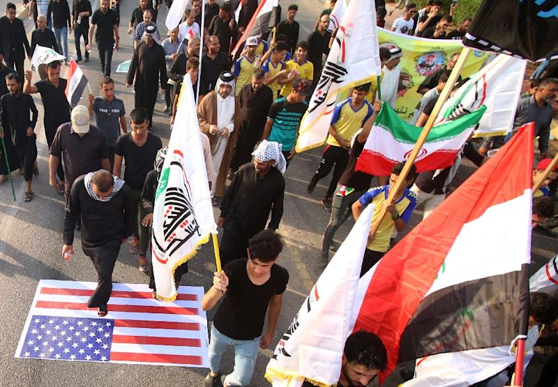 Iraqi demonstrators waving Iranian and pro-Iranian party flags step on a US flag during a protest on September 15, 2018 (AFP Photo/Haidar MOHAMMED ALI)
