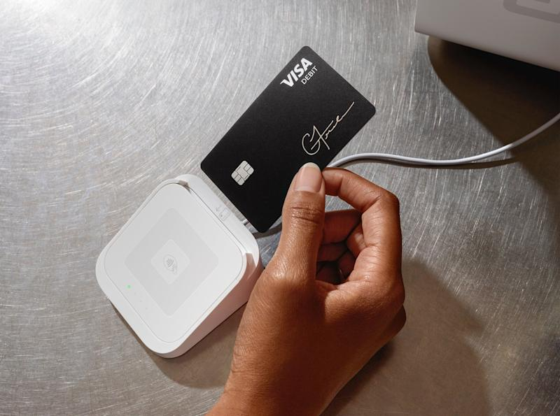 A person inserting their Cash Card into a Square chip-reading device.