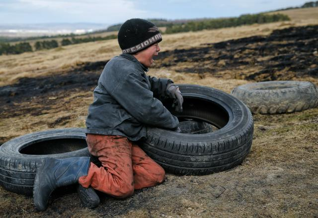 In this photo taken on Sunday, March 10, 2019, a child cries after arguing with another during a ritual marking the upcoming Clean Monday, the beginning of the Great Lent, 40 days ahead of Orthodox Easter, on the hills surrounding the village of Poplaca, in central Romania's Transylvania region. Romanian villagers burn piles of used tires then spin them in the Transylvanian hills in a ritual they believe will ward off evil spirits as they begin a period of 40 days of abstention, when Orthodox Christians cut out meat, fish, eggs, and dairy. (AP Photo/Vadim Ghirda)
