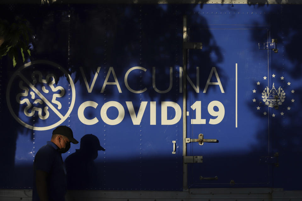 A driver walks past a refrigerated container truck from the Health Ministry that will transport doses of COVID-19 vaccines which El Salvador's government is donating and delivering to neighboring Honduras, shortly before departing San Salvador, El Salvador, Thursday, May 13, 2021. (AP Photo/Salvador Melendez)