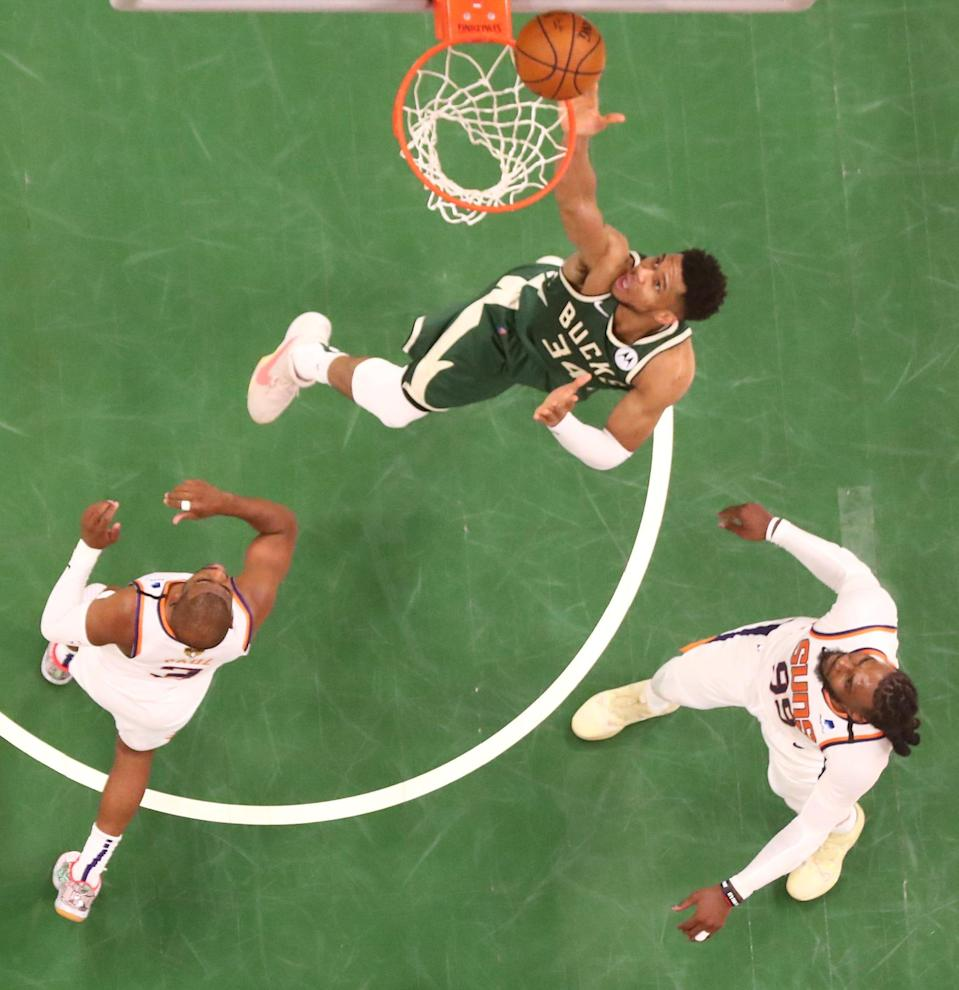Milwaukee Bucks forward Giannis Antetokounmpo (34) shoots over Phoenix Suns forward Jae Crowder (99) and guard Chris Paul (3) during game three of the 2021 NBA Finals at Fiserv Forum.
