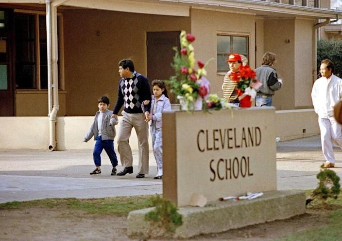 A man and two students arrive back at Cleveland Elementary School in Stockton, Calif., Jan. 17, 1989 after a heavily armed gunman invaded the school yard and killed five children and injured 30 others before killing himself. (AP Photo/Paul Sakuma)