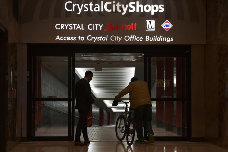 FILE- In this Tuesday, Nov. 13, 2018, file photo, people walk in Crystal City, Va. Washington, D.C.'s subway system, which serves the Crystal City, Va., neighborhood that Amazon chose for one of its headquarters locations, is at capacity on many of its lines and has serious maintenance problems, said Tom Rubin, a transportation consultant based in Oakland, Calif. (AP Photo/Susan Walsh, File)