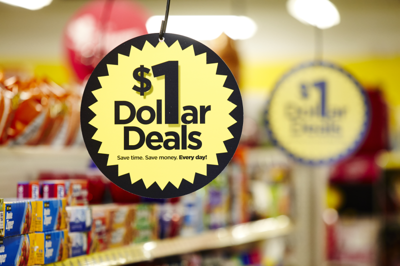 A sign in a dollar store aisle that says $1 Dollar Deals.