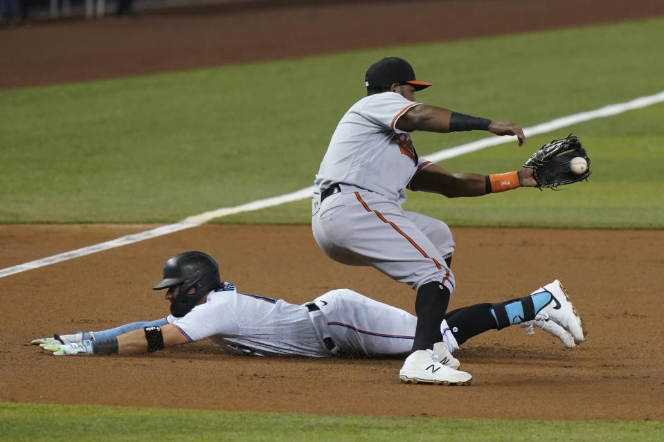 Miami Marlins' Miguel Rojas (19) slides into third base as Baltimore Orioles third baseman Maikel Franco (3) is late with the tag during the first inning of a baseball game, Tuesday, April 20, 2021, in Miami. (AP Photo/Marta Lavandier)