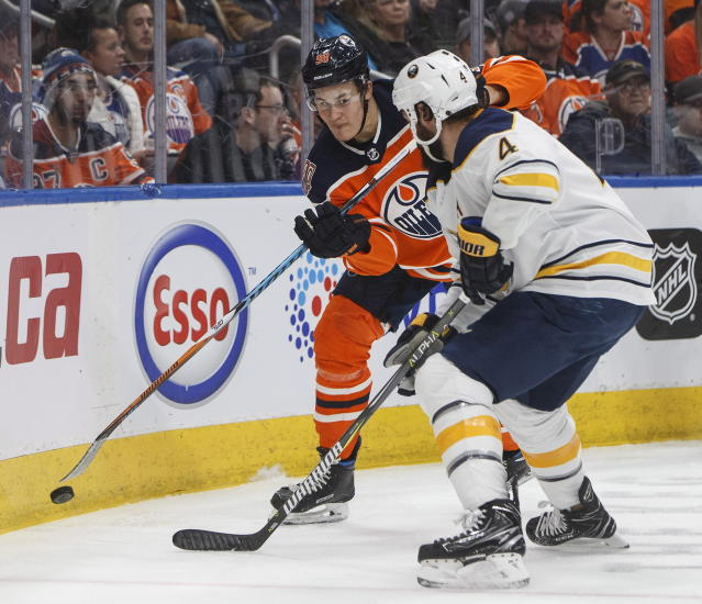 Buffalo Sabres' Zach Bogosian (4) and Edmonton Oilers' Jesse Puljujarvi (98) battle for the puck during second period NHL hockey action in Edmonton, Alberta, on Monday, Jan. 14, 2019. (Jason Franson/The Canadian Press via AP)