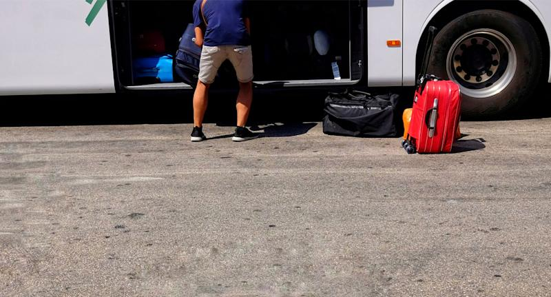 Photo shows the back of a man packing luggage into a bus.
