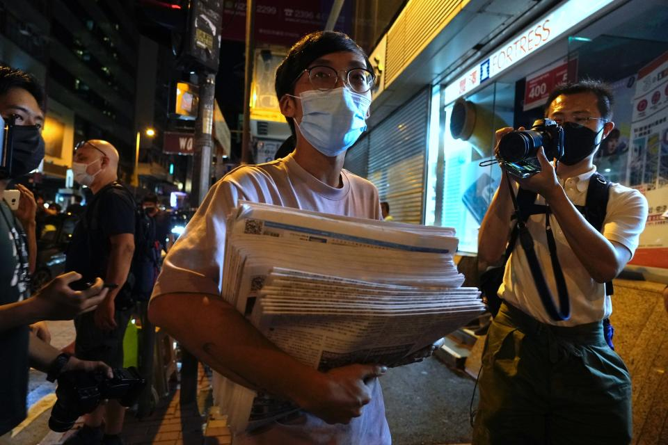 A man holds a stack of last issue of Apple Daily after purchase at a newspaper booth in Hong Kong, early Thursday, June 24, 2021. Hong Kong's pro-democracy Apple Daily newspaper will stop publishing Thursday, following last week's arrest of five editors and executives and the freezing of $2.3 million in assets under the city's year-old national security law. ( AP Photo/Vincent Yu)