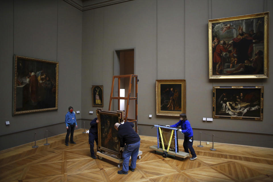 Workers at the Louvre museum handle a painting called Saint Louis, King of France, and his Page by Spanish painter El Greco, as it returns from an exhibition at the Chicago Institute, in the Louvre museum, in Paris, Tuesday, Feb. 9, 2021. (AP Photo/Thibault Camus)