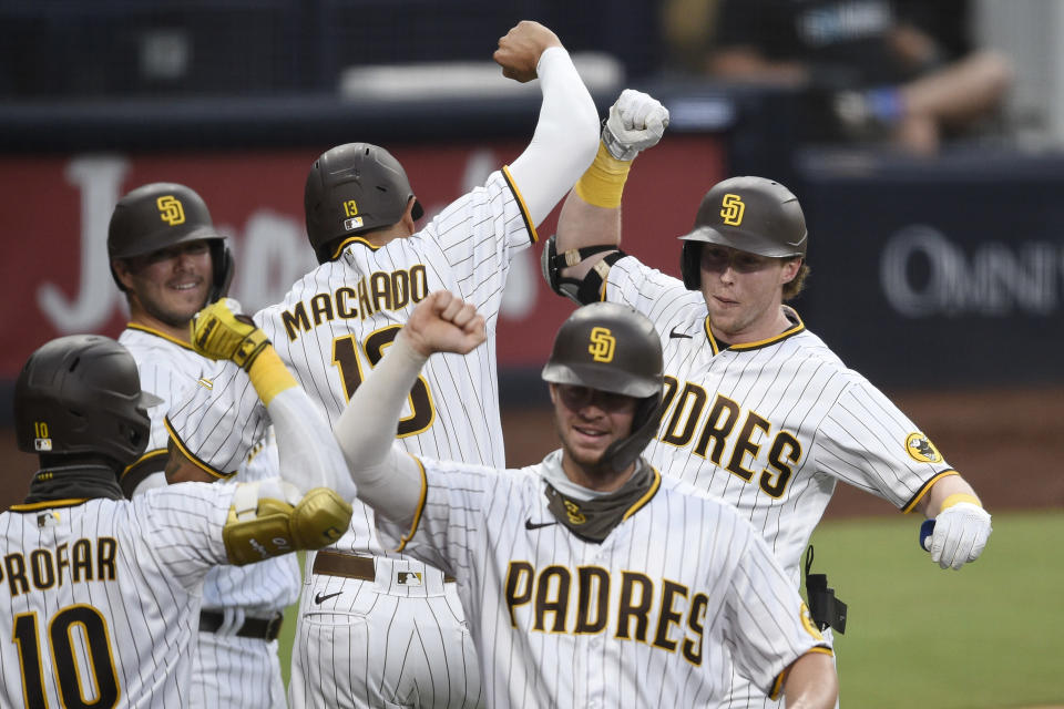 San Diego Padres' Jake Cronenworth, back right, celebrates his grand slam with Manny Machado during the second inning of the team's baseball game against the Houston Astros in San Diego, Saturday, Aug. 22, 2020. (AP Photo/Kelvin Kuo)