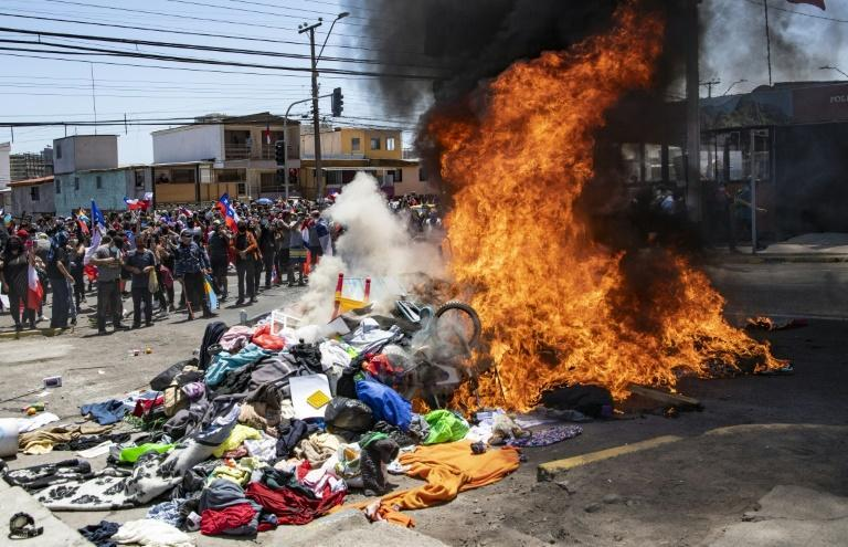 Demonstrators burn belongings at a makeshift Venezuelan migrant camp during a protest in Iquique, Chile on September 25, 2021 (AFP/MARTIN BERNETTI)
