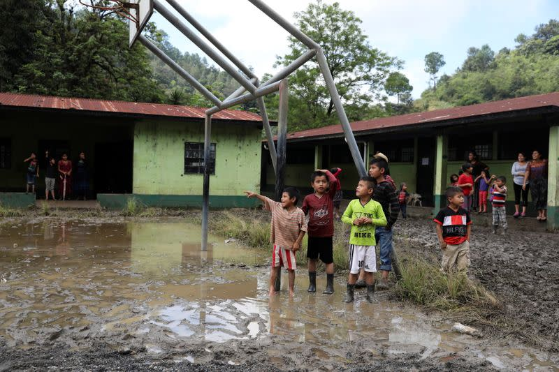 Children observe a helicopter landing at a school, being used as a temporary shelter for people from neighboring villages affected from the mudslides caused by heavy rains brought by Storm Eta, in the village of Santa Elena