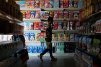 """A children passes in front of a shelf with cereal boxes at a """"bodegon"""" named """"Mini Walmart"""" in Puerto Cabello"""