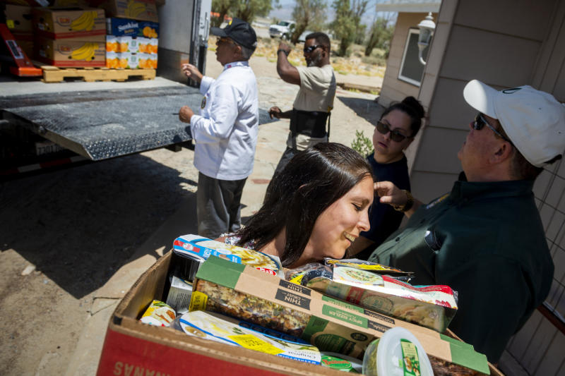 Julia Doss, foreground, helps unload a truck load of food at the Christian Fellowship of Trona, Calif., on Tuesday July 9, 2019. Desert Manna, and Darrin Fikstad, far right, offered a large truck full of food along with several other High Desert charities for the town ravaged by earthquakes and aftershocks. It could be several more days before water service is restored to the tiny town of Trona, where officials trucked in portable toilets and showers. (James Quigg/The Daily Press via AP)