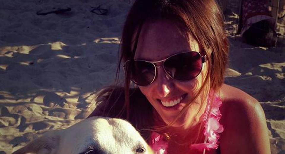 A woman wearing sunglasses smiling at the camera at the beach with a dog.