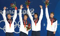 <p>(L-R) Michael Phelps, Ryan Lochte, Ricky Berens and Peter Vanderkaay pose with the gold medal on the podium during the medal ceremony for the Men's 4 x 200m freestyle relay final during the Beijing Olympic Games on August 13, 2008. The United States won the race in a time of 6:58.56, a new World Record. (Photo: Paul Gilham/Getty Images)</p>
