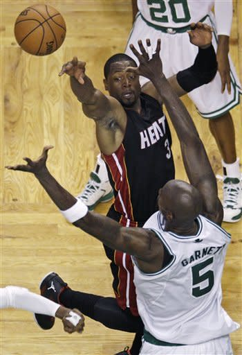 Miami Heat guard Dwyane Wade dumps off the ball as he is covered by Boston Celtics forward Kevin Garnett (5) on a drive to the basket during the second quarter of Game 3 in the NBA basketball playoffs Eastern Conference finals, in Boston on Friday, June 1, 2012. (AP Photo/Charles Krupa)
