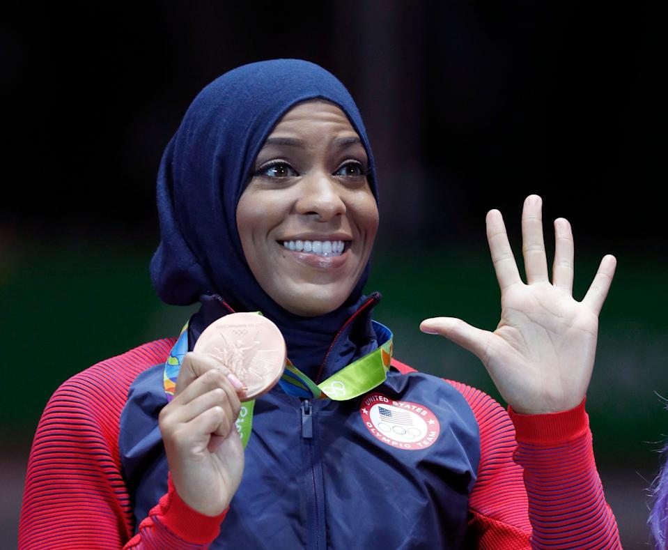 Ibtihaj Muhammad of the United States pose with her bronze medals on the podium after the womens team sabre fencing event at the 2016 Summer Olympics in Rio de Janeiro, Brazil, Saturday, Aug. 13, 2016. (AP Photo/Vincent Thian)