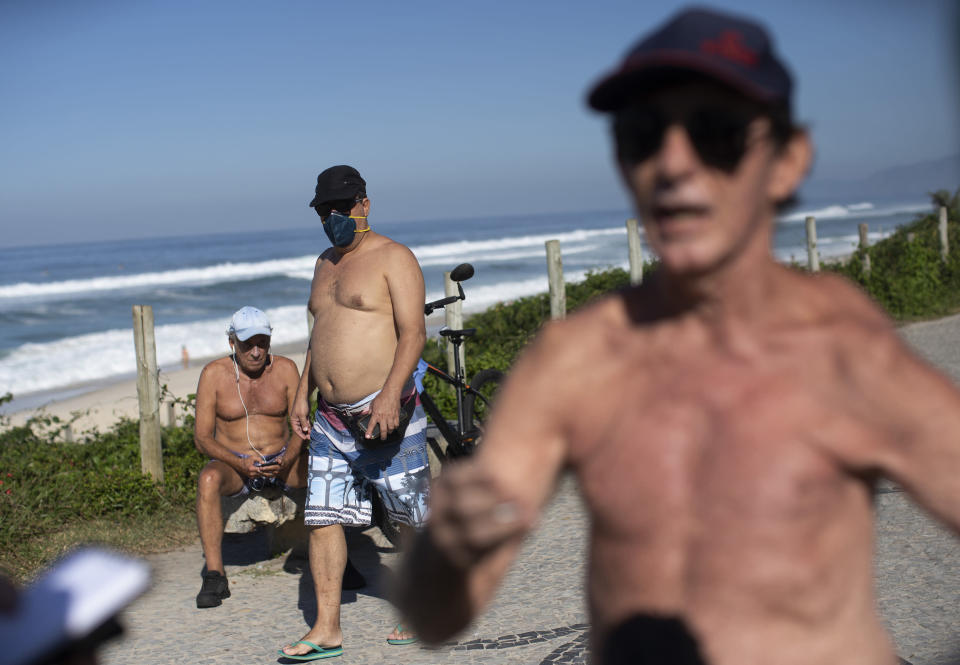 """People, one wearing a mask, rest and exercise along the seafront next to Barra de Tijuca beach, as Fernando Ferreira, right, speaks during an interview as he takes a walk outside amid the new coronavirus pandemic in Rio de Janeiro, Brazil, Wednesday, April 29, 2020. The retired dentist and lawyer recommended reading the Bible and Albert Camus' The Plague, citing them as evidence pandemics have always happened to some degree, and said restrictions on commerce are """"absurd."""" (AP Photo/Silvia Izquierdo)"""