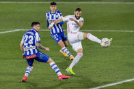 Real Madrid's Karim Benzema, right, tries a shot during the Spanish La Liga soccer match between Alaves and Real Madrid at Mendizorroza stadium in Vitoria, Spain, Saturday, Jan. 23, 2021. (AP Photo/Alvaro Barrientos)