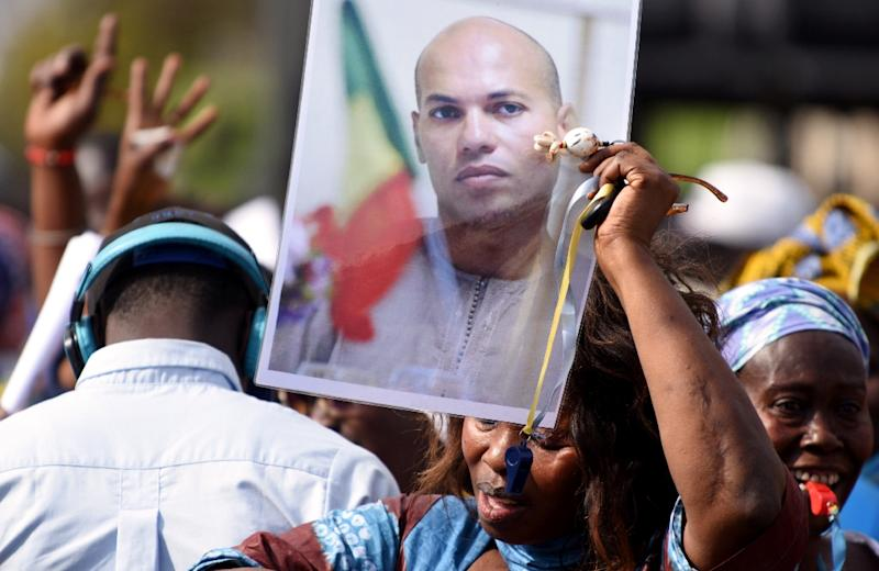 A woman holds up a photo of Karim Wade, former minister and son of former Senegalese President Abdoulaye Wade, at a meeting of the opposition at the Place de l'Obelisque in Dakar on February 4, 2015 (AFP Photo/Seyllou)