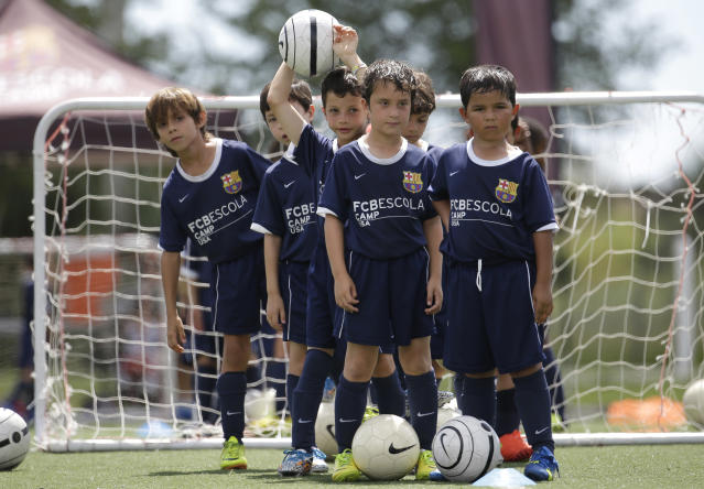 In this Thursday, Aug. 1, 2014 photo, children participate in a soccer camp held by FC Barcelona in Miami. European clubs like Barcelona, Liverpool and Arsenal have long sent coaches to work at U.S. summer camps, but now some are opening year-round U.S. academies aimed at finding new talent but also to expand their fan bases. This is part of a number of initiatives of major teams to grow their brands in the U.S. (AP Photo/Lynne Sladky)