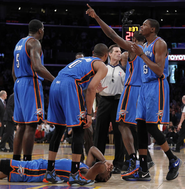 CORRECTS SPELLING OF NAME TO METTA, NOT META - Oklahoma City Thunder players stand over teammate James Harden, lower left, after receiving a flagrant double foul from Los Angeles Lakers' Metta World Peace, who was then ejected, in the first half of an NBA basketball game, Sunday, April 22, 2012, in Los Angeles. (AP Photo/Reed Saxon)