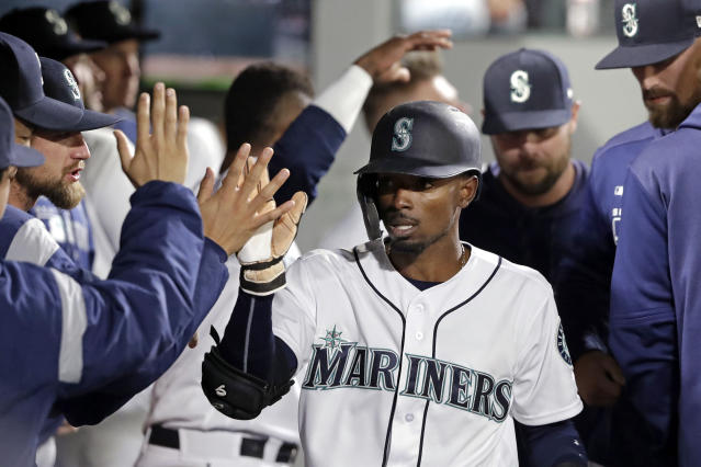 Seattle Mariners' Dee Gordon is congratulated in the dugout after scoring against the Los Angeles Angels in the sixth inning of a baseball game Tuesday, April 2, 2019, in Seattle. (AP Photo/Elaine Thompson)