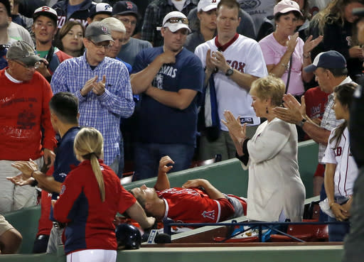 Fans applaud as Los Angeles Angels starting pitcher Garrett Richards is wheeled off the field after an injury during the second inning of a baseball game against the Boston Red Sox at Fenway Park in Boston, Wednesday, Aug. 20, 2014. (AP Photo/Elise Amendola)
