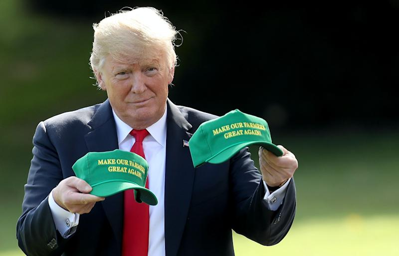 """President Donald Trump holds up two hats that say """"Make Our Farmers Great Again"""" as he departs the White House August 30, 2018 in Washington, DC. Trump is scheduled to attend events in Indiana later today. (Photo: Win McNamee/Getty Images)"""