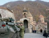 A service member of the Russian peacekeeping troops stands next to a military vehicle at Dadivank monastery in Kalbajar district