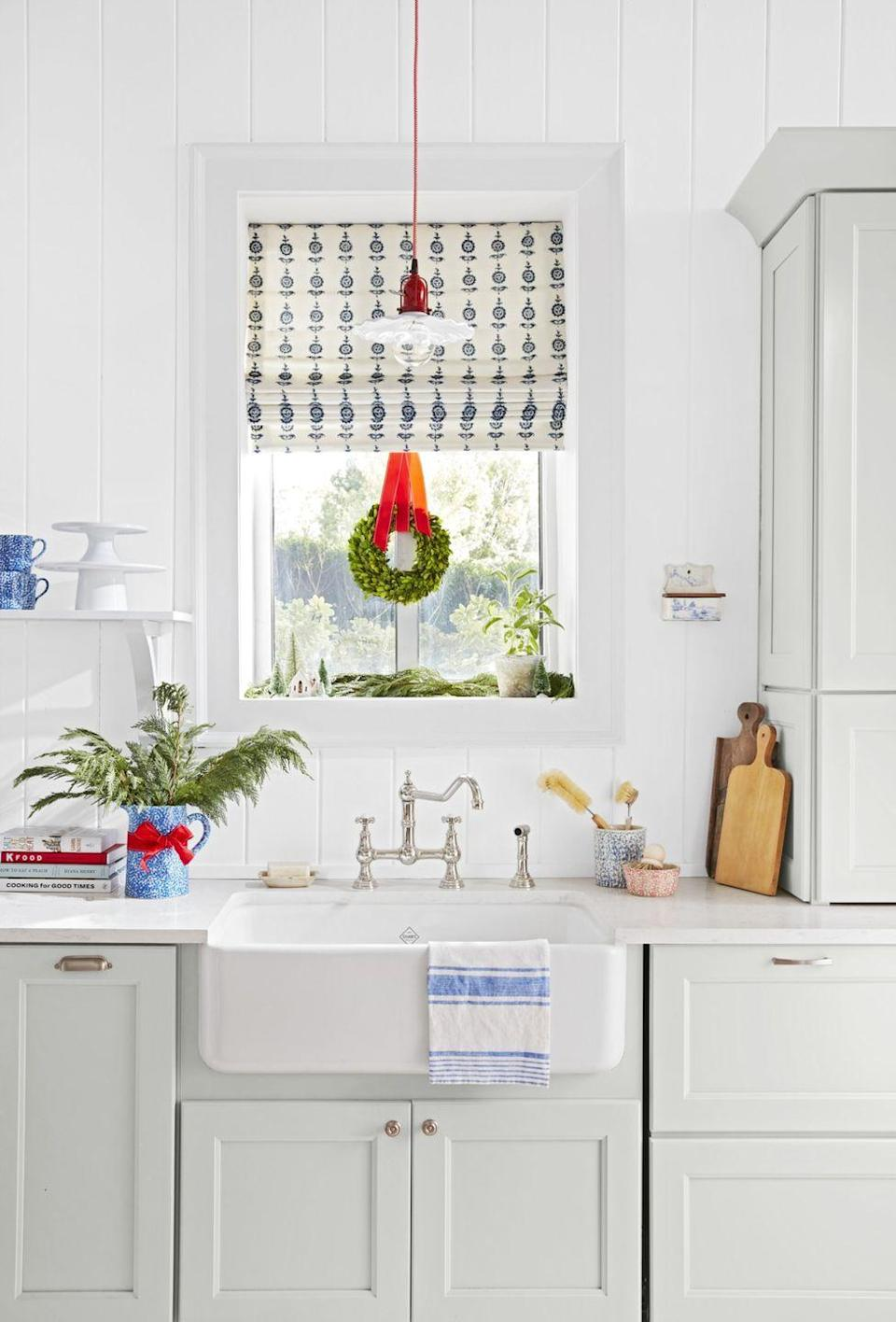 <p>You want to add some Christmas cheer to your kitchen, but you also don't want it to get in your way. A small wreath hanging from the window does the trick—and will remind you of the holiday season while you're washing dishes!</p>