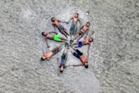 Friends play in the mud in Bangladesh. [Photo: SWNS]