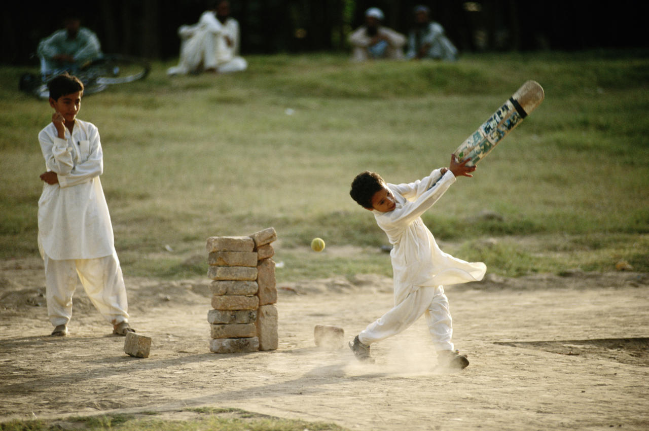 A group of young children use a stack of bricks as a wicket whilst playing cricket on 6 November 1994 in Lahore, Pakistan.(Photo by Shaun Botterill/Getty Images)