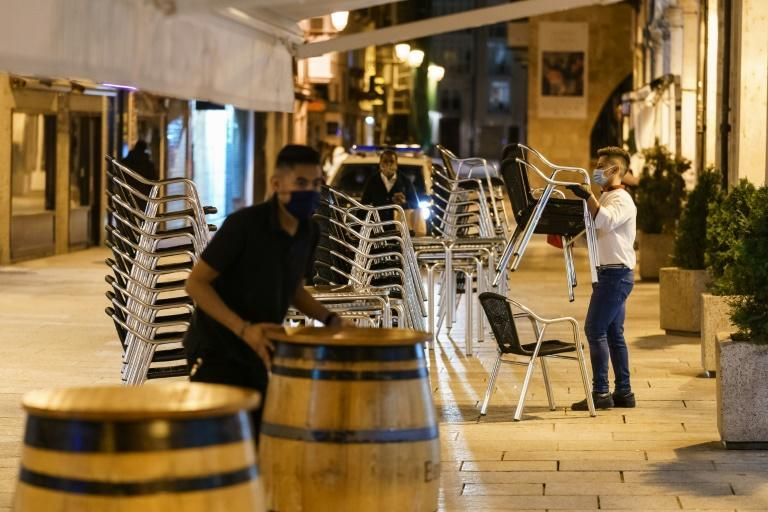 Barmen packed up a restaurant terrace in Spanish city Burgos after a curfew came into force on Saturday night