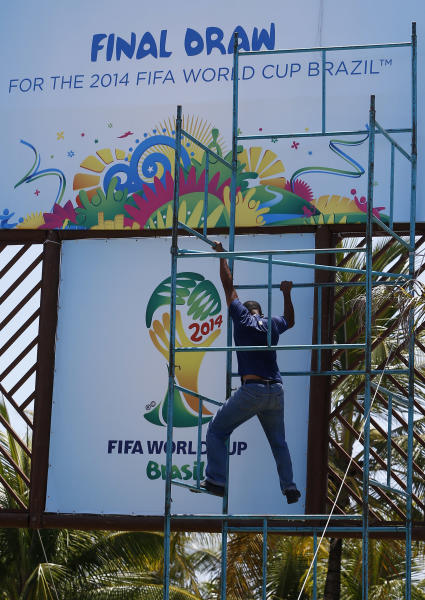 A worker climbs down a scaffold one day before the draw for the 2014 soccer World Cup in Costa do Sauipe near Salvador, Brazil, Thursday, Dec. 5, 2013. (AP Photo/Victor Caivano)