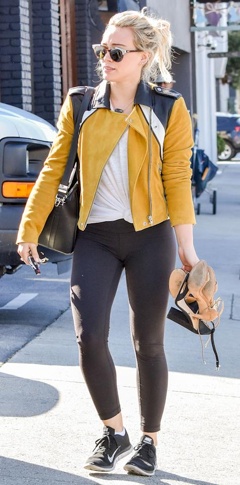 """<p>The actress mixed athleisure and street style pairing black leggings, Nike sneakers ($110; <a rel=""""nofollow"""" href=""""https://click.linksynergy.com/fs-bin/click?id=93xLBvPhAeE&subid=0&offerid=489843.1&type=10&tmpid=12957&RD_PARM1=http%3A%2F%2Fstore.nike.com%2Fus%2Fen_us%2Fpd%2Fair-zoom-pegasus-33-womens-running-shoe%2Fpid-10944629%2Fpgid-11871146&u1=ISNewsHilaryDuffStreetStyle3.13JA"""">nike.com</a>), and a knotted white tee with a yellow leather jacket and a structured black purse. </p>"""