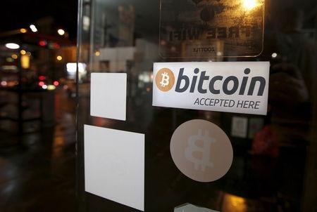 A bitcoin sticker is seen in the window of the 'Vape Lab' cafe, where it is possible to both use and purchase the bitcoin currency, in London March 24, 2015. REUTERS/Peter Nicholls/Files