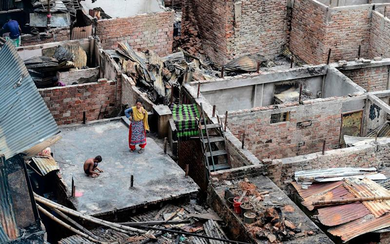 A child plays on a roof of a burnt house in a slum in Dhaka - AFP