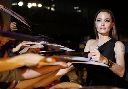 """Hollywood actress Angelina Jolie gives her autograph to fans at the Japan premiere of her partner Brad Pitt's movie """"World War Z"""" in Tokyo July 29, 2013. REUTERS/Issei Kato/Files"""
