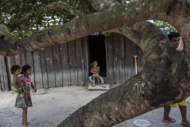 "In this Sept. 2, 2019 photo, Tembe children tend to the toddlers, as residents begin to gather for lunchtime in the Ka 'a kyr village, in Para state, Brazil. ""This is paradise,"" Muti Tembe said. ""You don't see any smoke from cars that pollute because we don't have any. In the city, at midday it gets too hot. ... Here, you're at ease and you don't hear the noises. Only the calls of birds."" (AP Photo/Rodrigo Abd)"