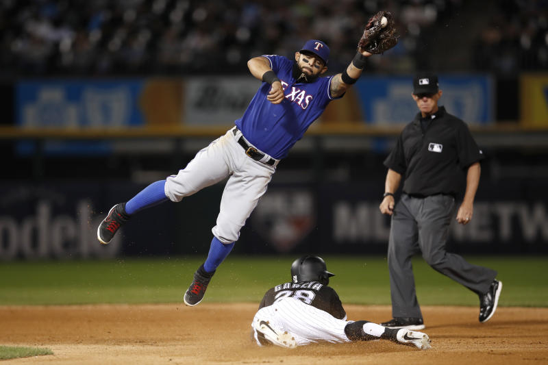 Chicago White Sox's Leury Garcia steals second base as Texas Rangers second baseman Rougned Odor, left, reaches for the throw as umpire Jim Wolf watches during the fourth inning of a baseball game Thursday, Aug. 22, 2019, in Chicago. (AP Photo/Jeff Haynes)