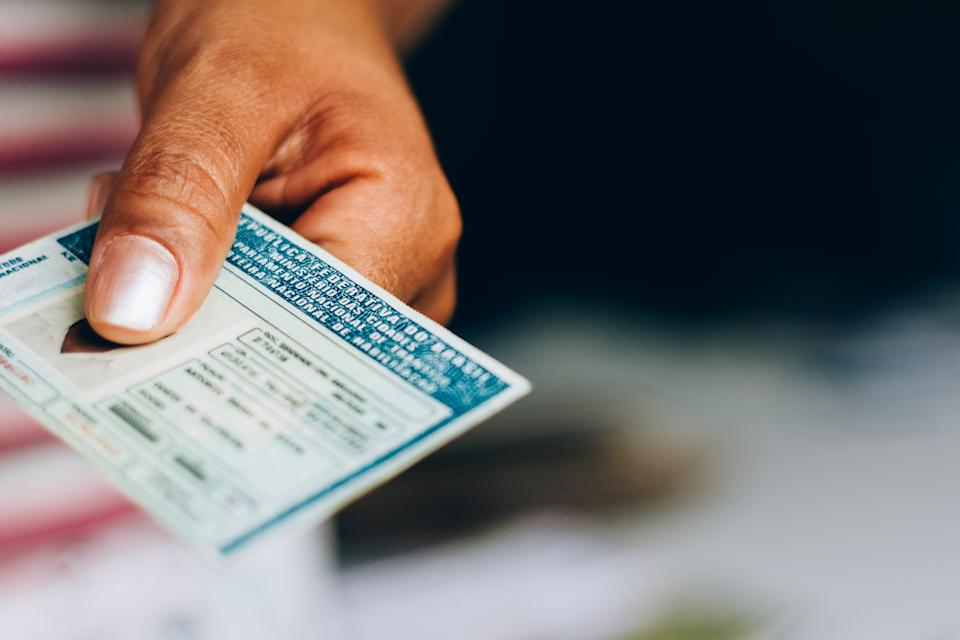 Man holds National Driver's License (CNH). Official document of Brazil, which attests the ability of a citizen to drive land vehicles.